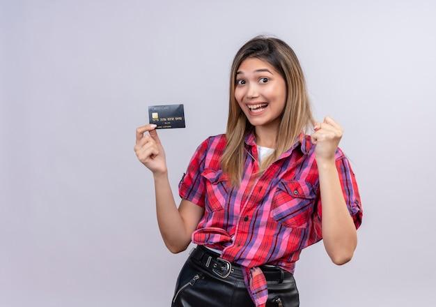 Милая молодая женщина в клетчатой рубашке улыбается, показывая кредитную карту со сжатым кулаком на белой стене