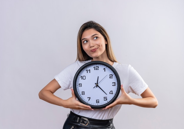 Милая молодая женщина в белой футболке держит настенные часы, глядя в сторону на белой стене