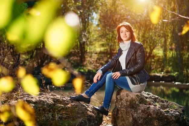 素敵な若い女性が太陽の下で秋の公園で池のそばの岩の上に座っています。