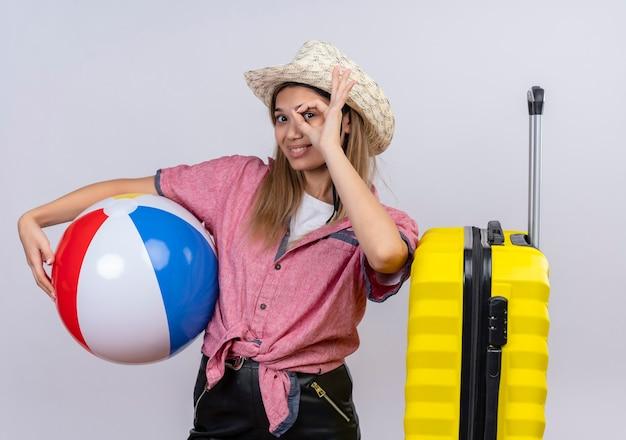 Милая молодая женщина в красной рубашке и шляпе от солнца держит надувной мяч и кладет руку на желтый чемодан, показывая жест на белой стене