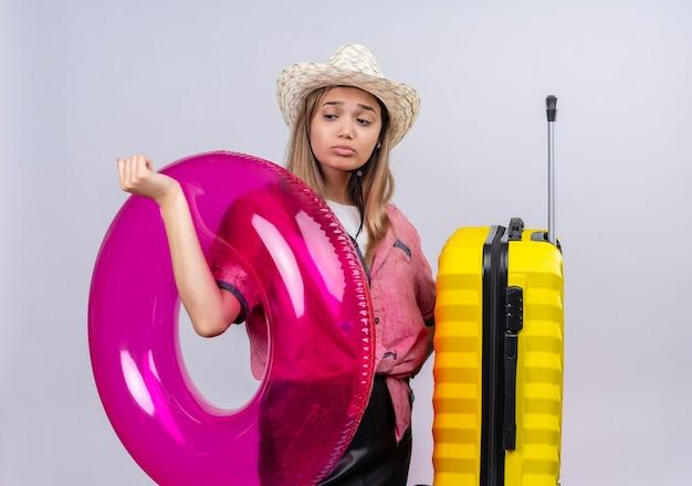 白い壁に黄色のスーツケースと膨脹可能なリングを保持しながら悲しそうに見える赤いシャツと日よけ帽を身に着けている素敵な若い女性