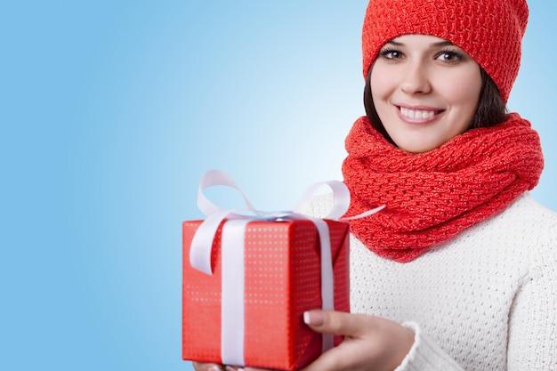 魅力的な笑顔と素敵な茶色の目、スカーフと白いセーターと赤い帽子をかぶっている素敵な若い女性