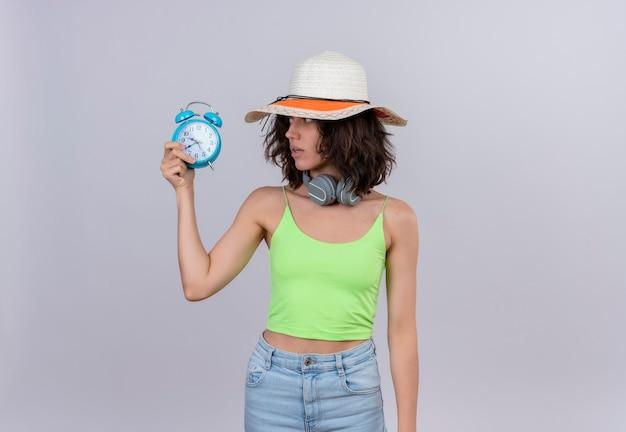 Милая молодая женщина с короткими волосами в зеленом топе в шляпе от солнца смотрит на синий будильник на белом фоне