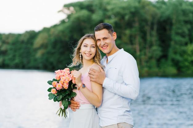 男と女が川や湖のほとりに立っている愛情のあるカップル