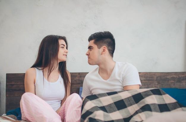 사랑하는 부부가 침대에 누워 있습니다. 밝고 아늑한 침실. 가족의 위안과 사랑.