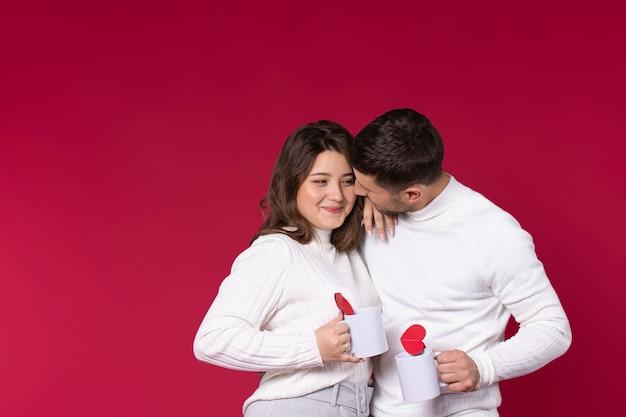 Влюбленная пара мило беседует на красном фоне с чашкой чая.