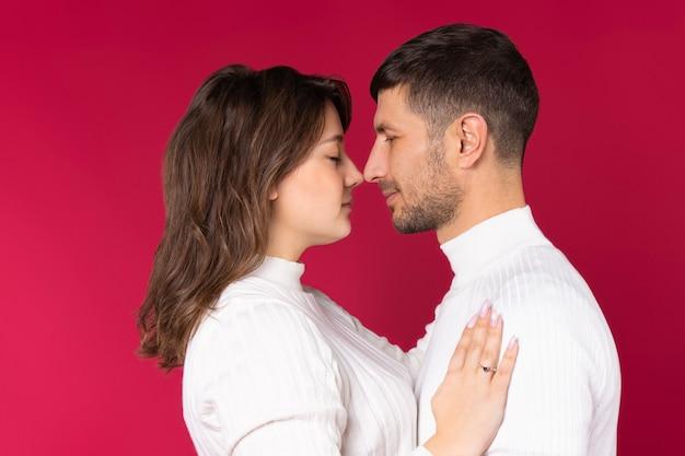 Влюбленные нежно обнимают друг друга. чувственная привязанность на красном фоне.