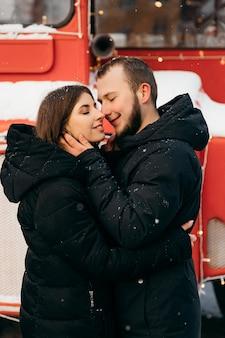 Влюбленная пара обнимается на фоне красного автобуса. день святого валентина. фото высокого качества