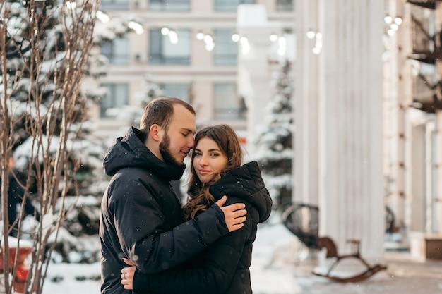 Влюбленная пара в нежных объятиях на фоне заснеженного города