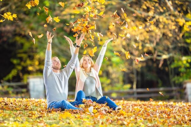 秋の公園で愛するカップルが葉の上に横たわっています。