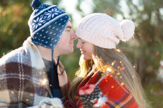 暖かい格子縞の愛情のあるカップルが線香花火を手に持ってキスします