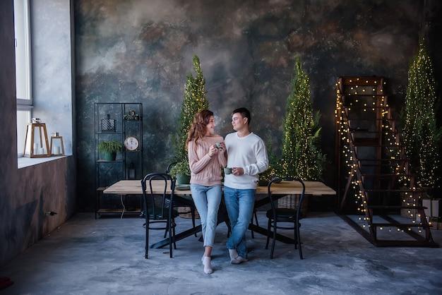 Влюбленная пара в теплых свитерах держит бирюзовые керамические чашки, горячие напитки в рождественских огнях
