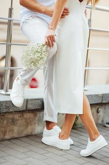白い服とスニーカーの愛情のあるカップルが手で抱擁します。未来との関係の概念
