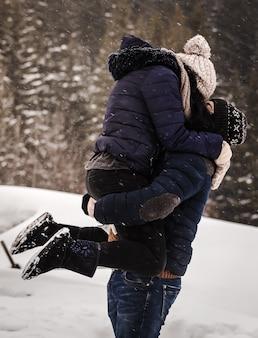 소나무 숲의 배경에 눈이 내리는 동안 겨울 옷을 입은 사랑하는 부부