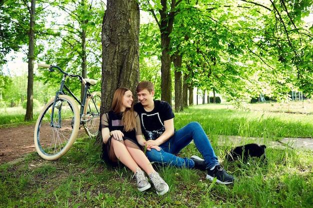 사랑의 부부는 공원에서 잔디에 나무에 의해 쉬고 있습니다.