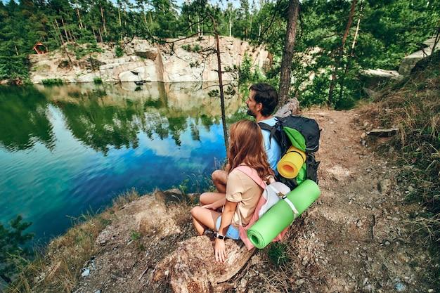 バックパックとラバーマットを持った愛情のこもったハイカーのカップルが湖のほとりに座って景色を楽しんでいます。キャンプ、旅行、ハイキング。