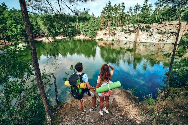 バックパックとラバーマットを持った愛情のこもったハイカーのカップルが湖のそばに立ち、景色を楽しんでいます。キャンプ、旅行、ハイキング。