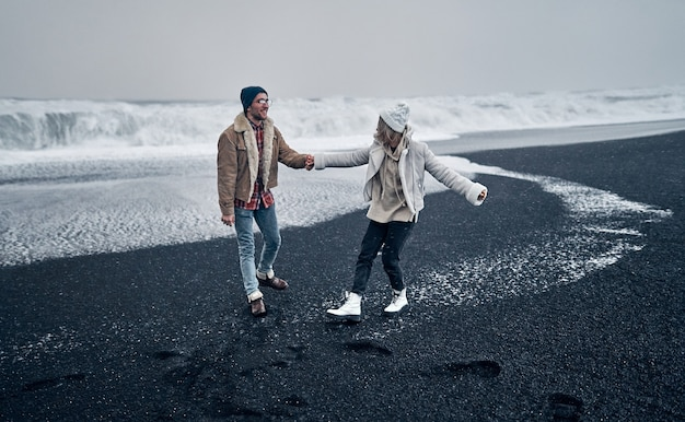 Влюбленная пара туристов, взявшись за руки, развлекается, гуляя по пляжу с черным вулканическим песком и любуясь великолепными океанскими волнами. путешествия, отдых, туризм.