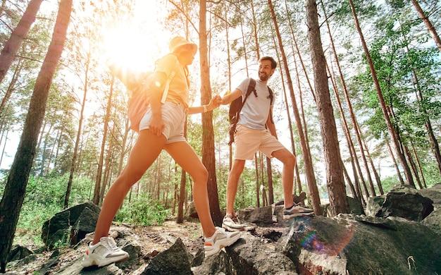 バックパックを持った愛情のこもった観光客のカップルが森の岩だらけの山頂を登ります。キャンプ、旅行、ハイキング。