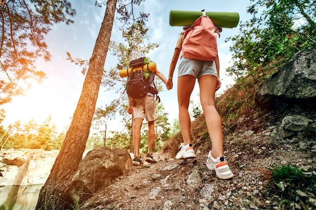 Влюбленная пара туристов с рюкзаками поднимается на скалистые вершины в лесу. походы, путешествия, походы.