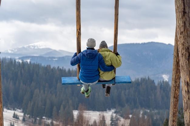 Влюбленная пара на качелях в зимних горах отношения отпуск путешествия концепция