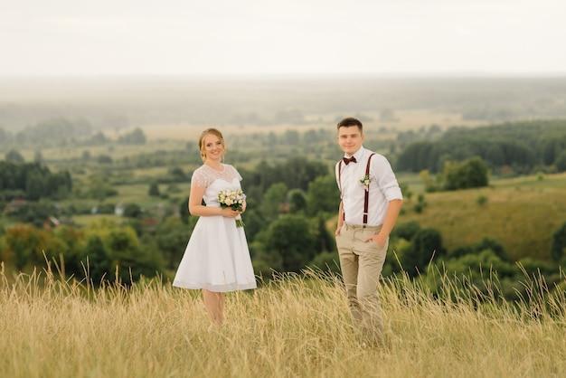 美しい景色に対してポーズをとって愛するカップル。結婚式の日。新郎新婦。