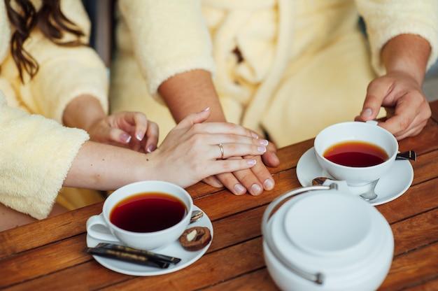 Влюбленная пара сидит в халатах и пьет чай на деревянном столе