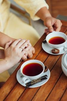 사랑하는 부부는 드레싱 가운에 앉아 나무 테이블에 차를 마신다.