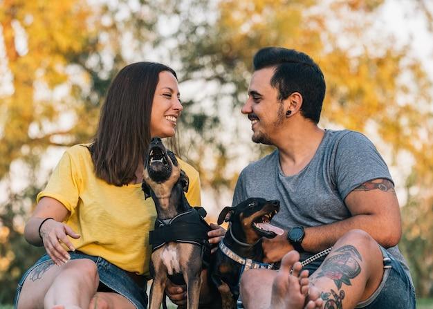 Влюбленная пара, сидящая на траве. молодая счастливая пара, глядя друг на друга со своими собаками в парке