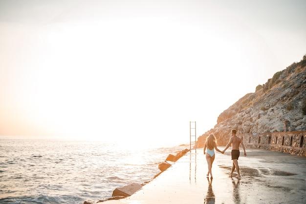 사랑하는 부부가 해변을 따라 바다를 걷고 있습니다. 지중해 일몰에 젊은 가족. 휴가 개념입니다. 바다에서 해질녘에 수영복을 입은 여자와 반바지를 입은 남자. 선택적 초점입니다.