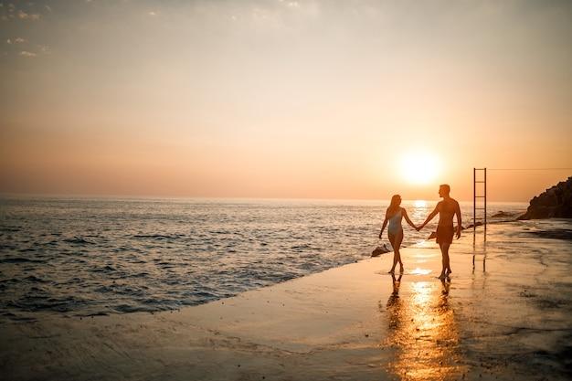 愛するカップルが海沿いのビーチを散歩します。地中海に沈む夕日の若い家族。休暇の概念。海に沈む夕日に水着姿の女性とショートパンツ姿の男性。セレクティブフォーカス。