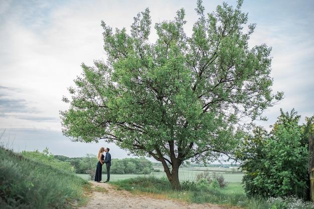 愛するカップルが畑を歩いていると、女の子は妊娠しています。新鮮な空気の中を歩きます。愛とケア。