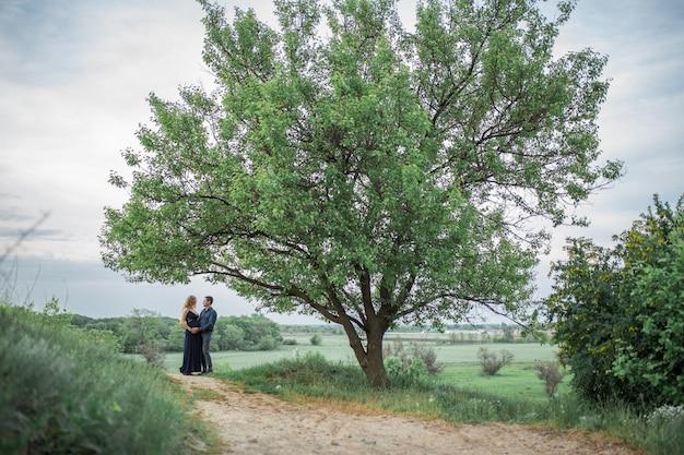 사랑하는 부부가 들판을 걷고, 소녀는 임신했습니다. 신선한 공기를 마시 며 걸어보세요. 사랑과 보살핌.