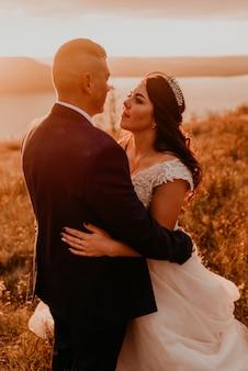 Влюбленная пара, свадебные молодожены в белом платье и костюме, гуляют, обнимаются, целуют водоворот на высокой траве в летнем поле на горе над рекой