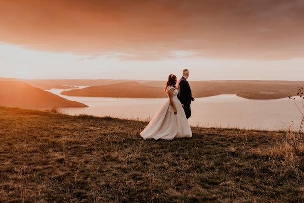 Влюбленная пара свадьбы молодожены гуляют летом осенью на горе на скале над рекой