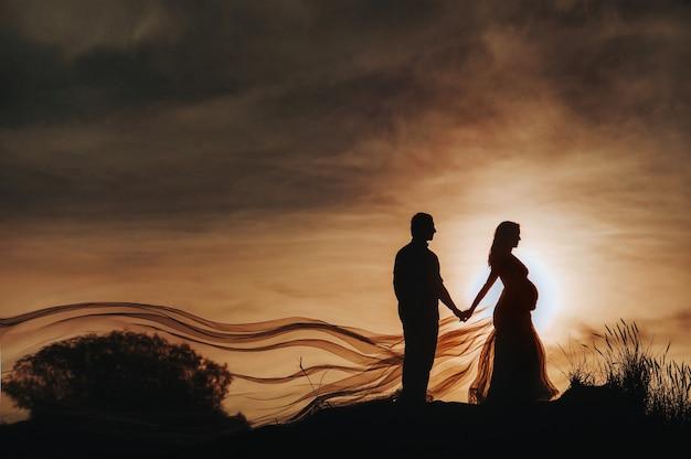 사랑하는 남자가 모래 언덕에서 일몰에 임산부 옆에 선다. 인식 할 수없는 초상화 아기를 기대하는 아름 다운 신혼 부부의 리투아니아, nida.