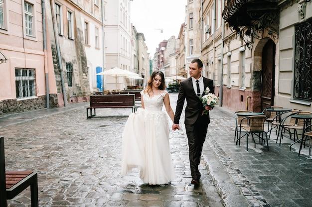 Влюбленная свадебная пара гуляет по улицам города львова. гуляют молодожены. свадебные прогулки.