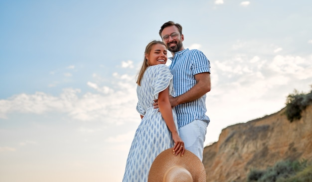 Влюбленная молодая пара обнимаются на берегу моря, наслаждаясь друг другом и отдыхом. на пляже обнимаются женщина в платье и мужчина в рубашке и белых брюках.