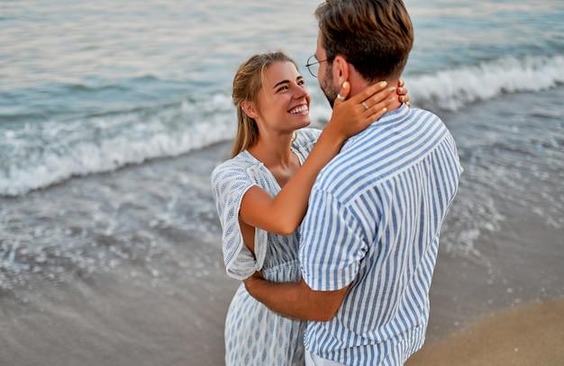 Влюбленные молодые пары обнимаются на берегу моря, наслаждаются друг другом и отдыхом, романтически проводят время на пляже.