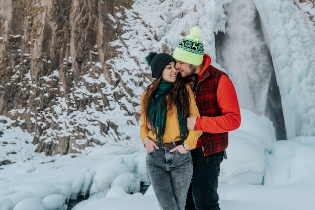 休暇中の冬の山で愛する若いカップル。男と女は旅行中です。