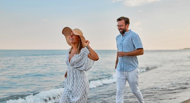 Влюбленная молодая пара бегает по берегу моря, наслаждаясь друг другом и отдыхом, веселится на пляже.