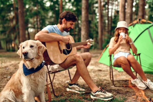 사랑하는 젊은 부부는 모닥불과 텐트 근처에 앉아 커피를 마시고 소나무 숲에서 래브라도 강아지와 기타를 연주합니다. 캠핑, 레크리에이션, 하이킹.