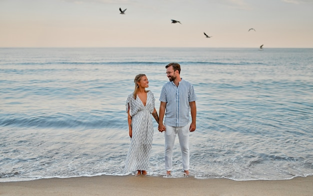 Влюбленная молодая пара гуляет по берегу моря, держась за руки, наслаждаясь друг другом и отдыхом, романтически проводя время на пляже.