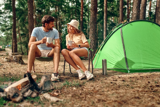 愛する若いカップルが週末にピクニックに行き、キャンプファイヤーとテントの近くに座って、松林でコーヒーを飲みました。キャンプ、レクリエーション、ハイキング。