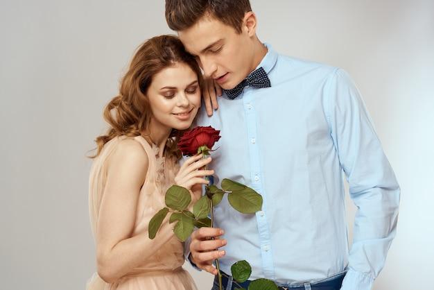 Влюбленная молодая пара с красной розой в руках на светлом фоне