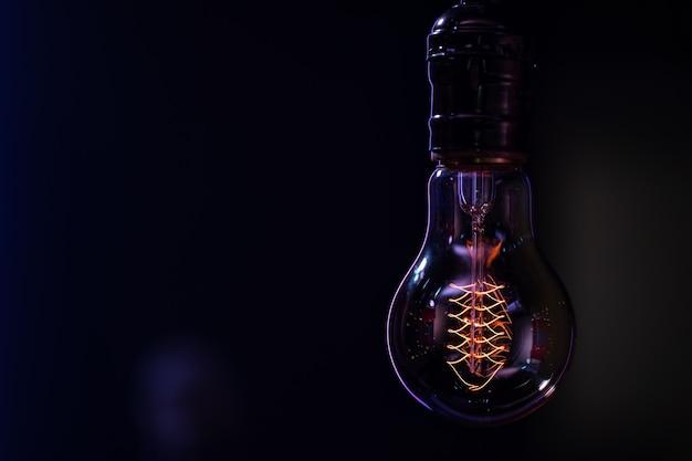 빛나는 램프는 어두운 배경을 흐리게 복사 공간에 달려 있습니다.
