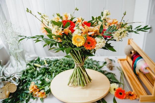 Пышный букет в стиле бохо на деревянной подставке на заваленном листьями и инструментами столе в мастерской флориста
