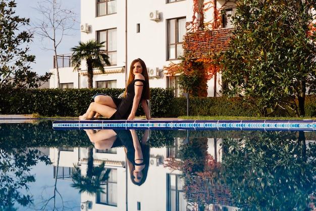 검은 드레스를 입은 호화로운 매력적인 여성이 푸른 수영장 옆에서 휴식을 취하고 풍요로운 삶을 즐긴다