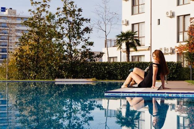 검은 드레스를 입은 고급스럽고 매력적인 젊은 여성이 햇살 아래 푸른 수영장 옆에서 휴식을 즐깁니다