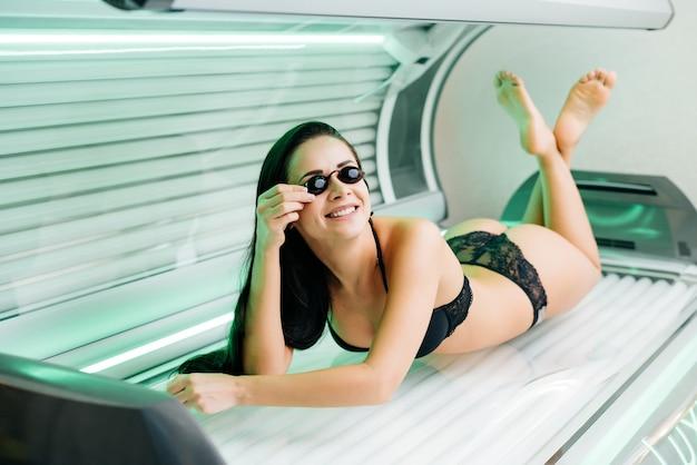 Роскошная красивая девушка лежит в горизонтальном солярии в защитных очках, загорая под ультрафиолетовыми лучами.